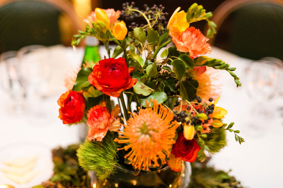 Winter Wedding Colors In Hues Of Reddish-Orange, Yellow & Green Create A Fireside Color Palette | Yellow Freesia, Pin Cushion Protea, Ranunculus, Carnation, Green Trick Dianthus Earthy Centerpiece