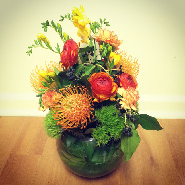 Winter Wedding Colors In Hues Of Reddish-Orange, Yellow & Green Create A Fireside Color Palette   Yellow Freesia, Pin Cushion Protea, Ranunculus, Carnation, Green Trick Dianthus Earthy Centerpiece